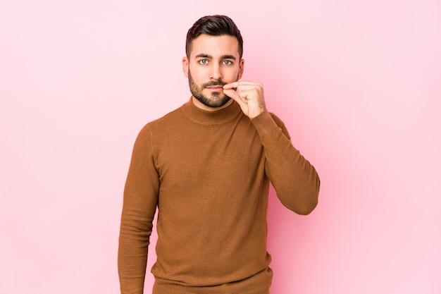 Młody caucasian mężczyzna przeciw różowej ścianie odizolowywającej z palcami na wargach utrzymuje sekret.