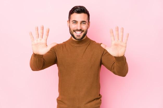 Młody caucasian mężczyzna przeciw różowej ścianie pokazuje liczbę dziesięć z rękami.