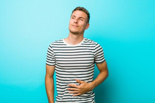 Młody caucasian mężczyzna przy błękitną ścianą dotyka brzuszek, uśmiecha się delikatnie, jedzenia i satysfakci pojęcie.