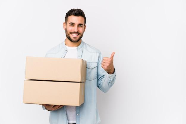 Młody caucasian mężczyzna rusza się do nowego domu odizolowywał uśmiecha się kciuk up i podnosi