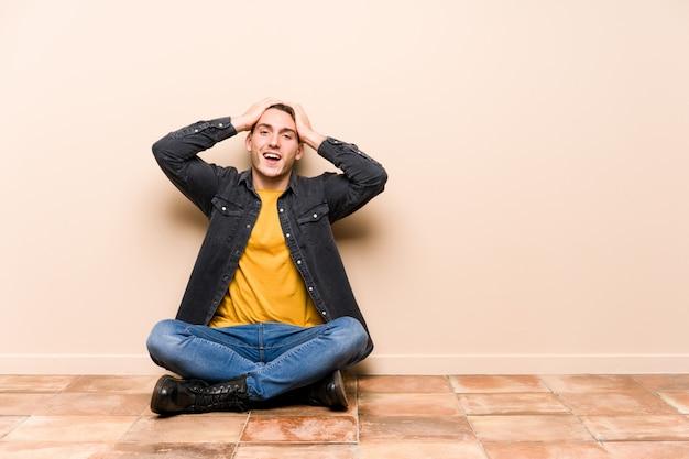Młody caucasian mężczyzna siedzi na podłoga odizolowywającej śmiechach radośnie trzyma ręki na głowie. koncepcja szczęścia.