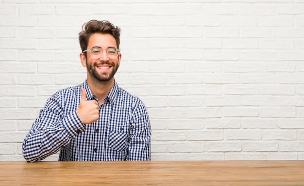 Młody caucasian mężczyzna siedzi rozochocony i excited, ono uśmiecha się i podnosi jej kciuk up, pojęcie sukces i zatwierdzenie, ok gest