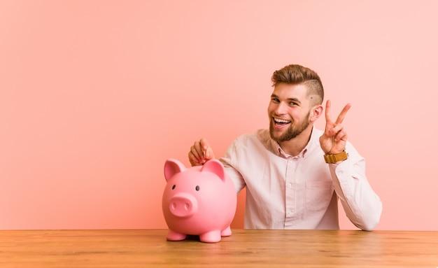 Młody caucasian mężczyzna siedzi z prosiątko bankiem pokazuje zwycięstwo znaka i uśmiecha się szeroko.