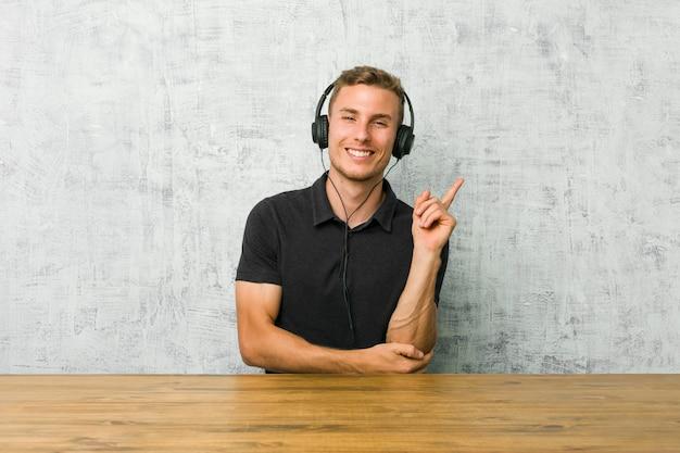 Młody caucasian mężczyzna słucha muzyka z hełmofonami ono uśmiecha się wesoło wskazuje z palcem wskazującym daleko od.