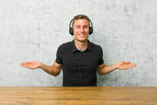 Młody caucasian mężczyzna słucha muzyka z hełmofonami pokazuje mile widziany wyrażenie.
