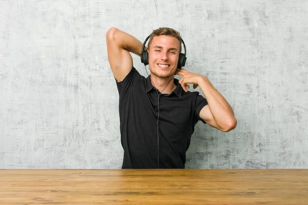 Młody caucasian mężczyzna słucha muzyka z hełmofonami rozciąga ręki, zrelaksowana pozycja.
