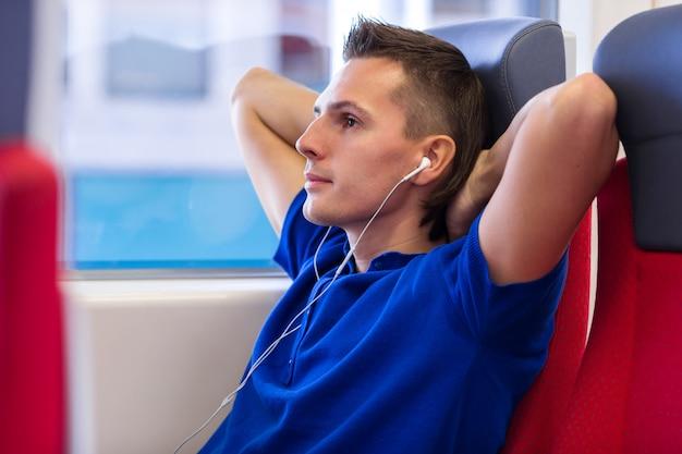 Młody caucasian mężczyzna słucha muzykę podróżuje pociągiem