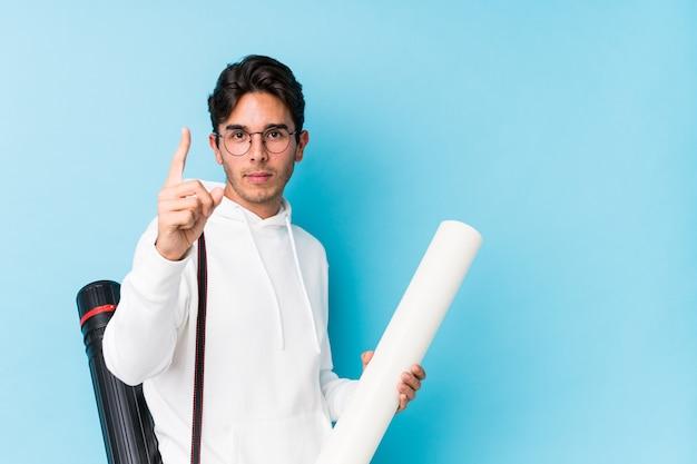 Młody caucasian mężczyzna studiuje architekturę odizolowywał pokazywać liczbę jeden z palcem.