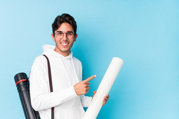 Młody caucasian mężczyzna studiuje architekturę odizolowywał uśmiecha się i wskazuje na boku, pokazuje coś przy pustą przestrzenią.