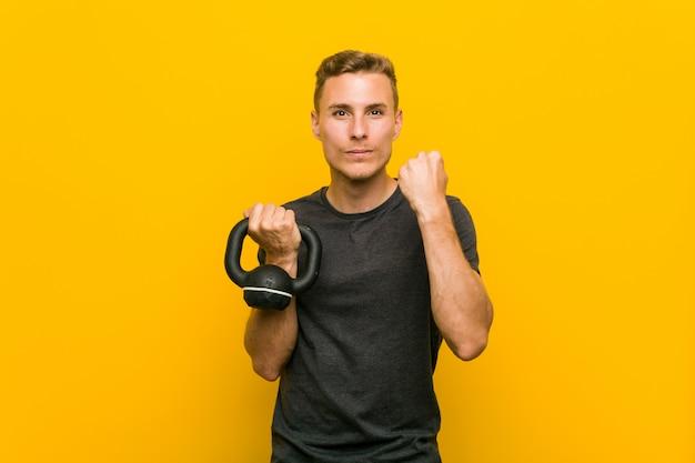 Młody caucasian mężczyzna trzyma dumbbell pokazuje pięść kamera, agresywny wyraz twarzy.
