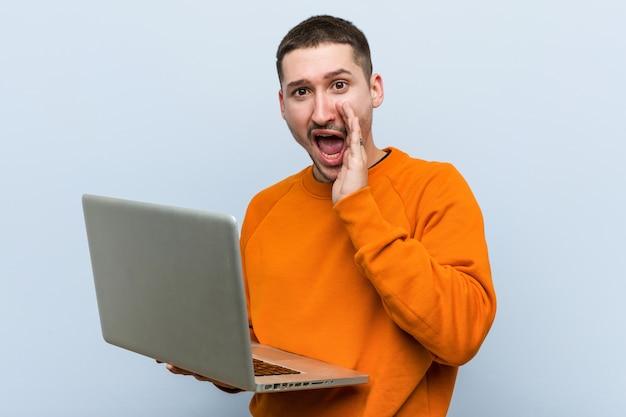 Młody caucasian mężczyzna trzyma laptop krzyczy podekscytowanego przód.