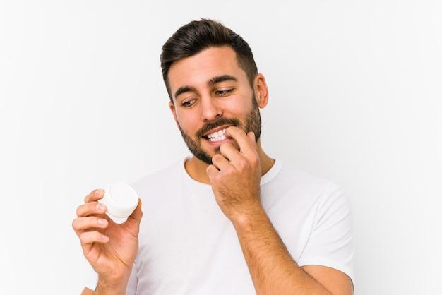 Młody caucasian mężczyzna trzyma moisturizer myśleć o coś