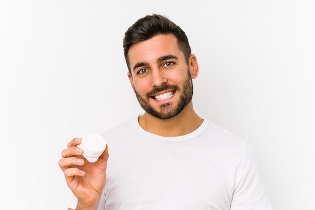 Młody caucasian mężczyzna trzyma moisturizer odizolowywał szczęśliwego, uśmiechniętego i rozochoconego.