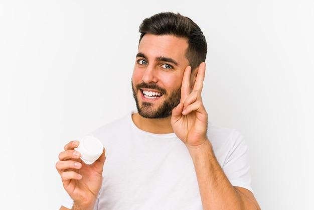 Młody caucasian mężczyzna trzyma moisturizer pokazuje zwycięstwo znaka i uśmiecha się szeroko.