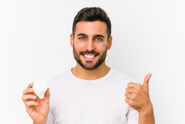 Młody caucasian mężczyzna trzyma moisturizer uśmiecha się kciuk up i podnosi