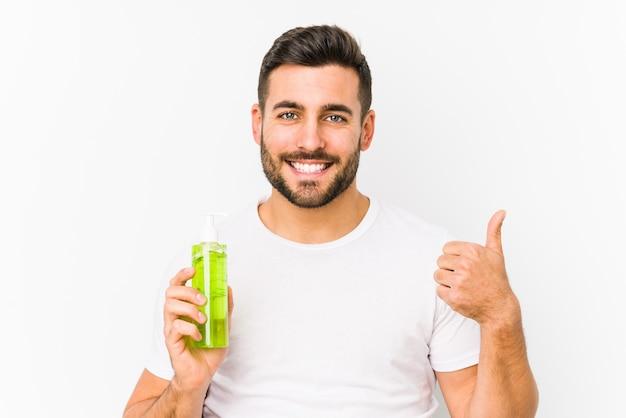 Młody caucasian mężczyzna trzyma moisturizer z aloesem odizolowywał uśmiecha się kciuk up i podnosi