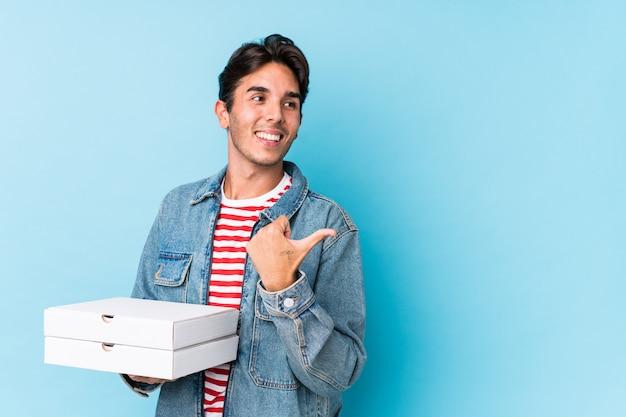 Młody caucasian mężczyzna trzyma pizze odizolowywał punkty z kciuka palcem daleko od, śmia się i beztroski.