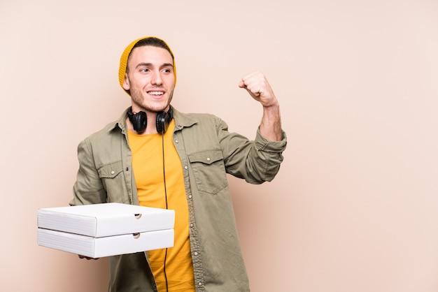 Młody caucasian mężczyzna trzyma pizze podnosi pięść po zwycięstwa
