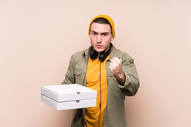 Młody caucasian mężczyzna trzyma pizze pokazuje pięść kamera, agresywny wyraz twarzy.
