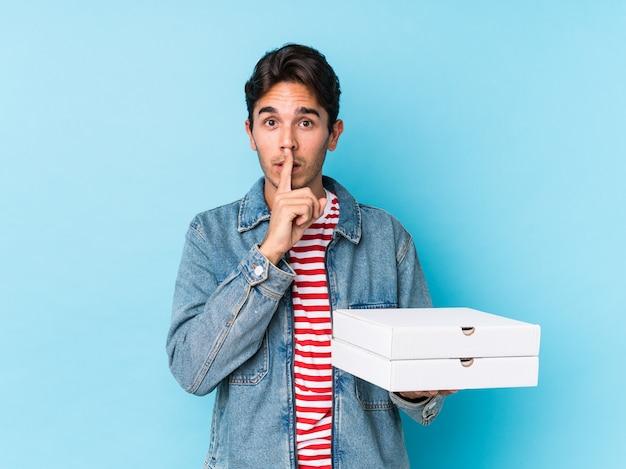 Młody caucasian mężczyzna trzyma pizze utrzymuje sekret