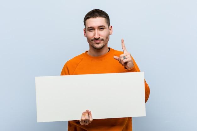 Młody caucasian mężczyzna trzyma plakat pokazuje liczbę jeden z palcem.