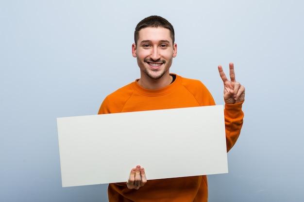 Młody caucasian mężczyzna trzyma plakat pokazuje zwycięstwo znaka i uśmiecha się szeroko.