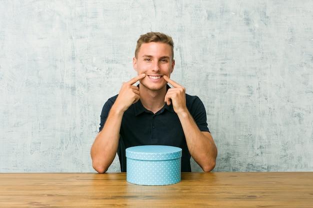 Młody caucasian mężczyzna trzyma prezenta pudełko stół wątpiący między dwiema opcjami.