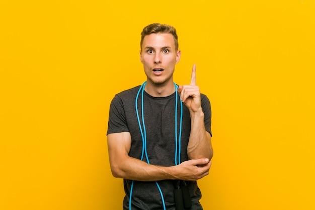Młody caucasian mężczyzna trzyma skokową arkanę ma niektóre doskonałego pomysł, pojęcie twórczość.