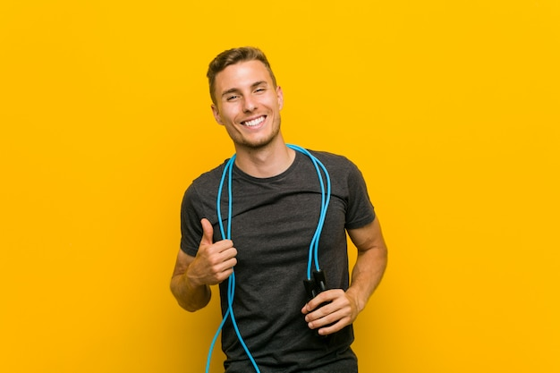 Młody caucasian mężczyzna trzyma skokową linę uśmiecha się kciuk up i podnosi