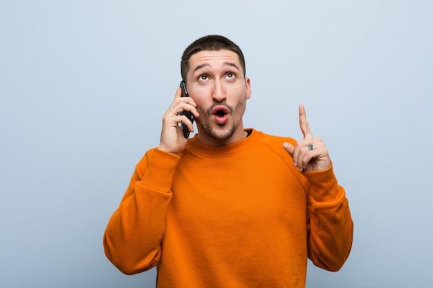 Młody caucasian mężczyzna trzyma telefon ma niektóre doskonałego pomysł, pojęcie twórczość.