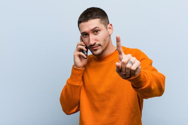Młody caucasian mężczyzna trzyma telefon pokazuje liczbę jeden z palcem.
