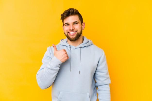Młody caucasian mężczyzna uśmiecha się kciuk up i podnosi na kolor żółty ścianie