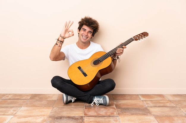 Młody caucasian mężczyzna z gitary obsiadaniem na podłoga pokazuje ok znaka z palcami