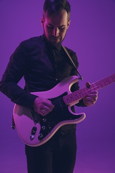 Młody caucasian muzyk bawić się gitarę w neonowym świetle na purpurach
