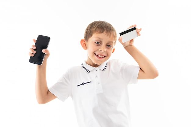 Młody caucasian nastolatek trzyma pieniądze kartę i jego telefon odizolowywający na bielu