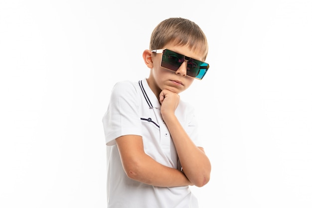 Młody caucasian nastolatek w dużych okularach przeciwsłonecznych na białym tle