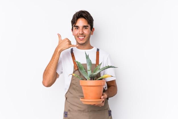 Młody caucasian ogrodniczka mężczyzna trzyma rośliny odizolowywającej pokazywać telefonu komórkowego wezwania gest z palcami.