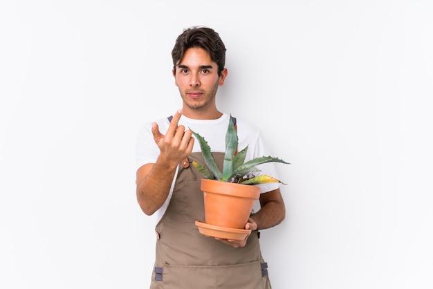 Młody caucasian ogrodnika mężczyzna trzyma rośliny odizolowywał wskazywać z tobą palcem tak jakby zapraszający zbliżał się.