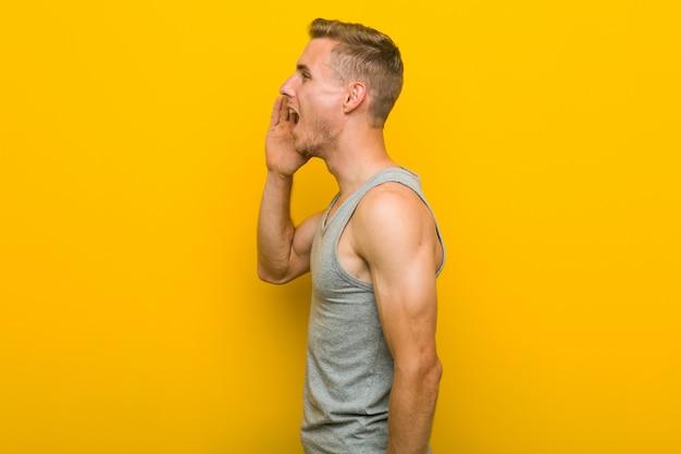Młody caucasian sporta mężczyzna krzyczy palmowego pobliskiego usta i trzyma blisko.