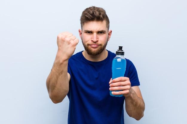 Młody caucasian sportowiec trzyma izotonicznego napój pokazuje pięść kamera, agresywny wyraz twarzy.
