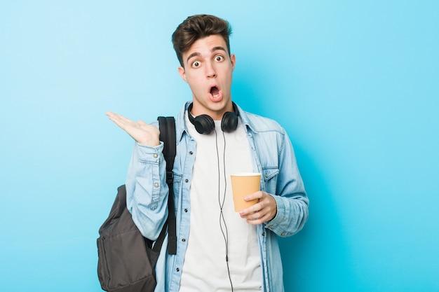 Młody caucasian studencki mężczyzna trzyma bierze oddaloną kawę imponującą mienie kopii przestrzeń na palmie.