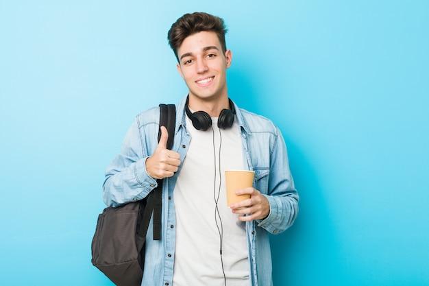Młody caucasian studencki mężczyzna trzyma bierze oddaloną kawę uśmiecha się kciuk up i podnosi