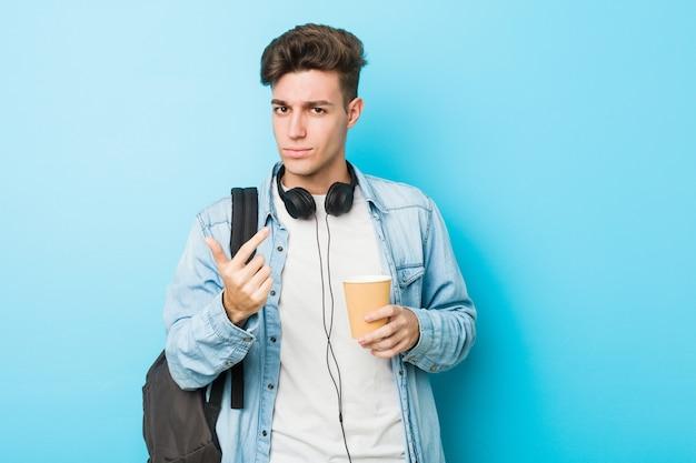 Młody caucasian studencki mężczyzna trzyma na wynos kawę wskazuje z palcem na ciebie, jakby zapraszający zbliżał się.
