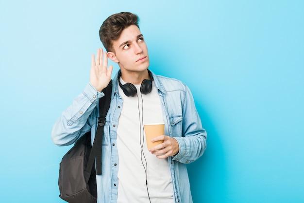 Młody caucasian studencki mężczyzna trzyma zabiera kawę próbuje słuchać plotki.