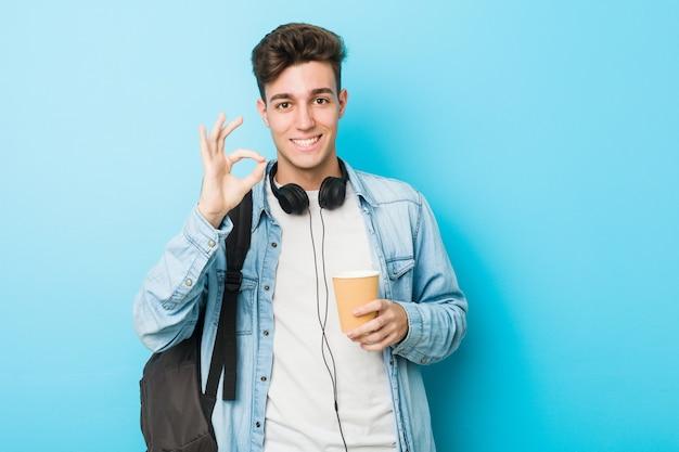 Młody caucasian studencki mężczyzna trzyma zabiera kawową rozochoconą i ufną pokazuje ok gest.
