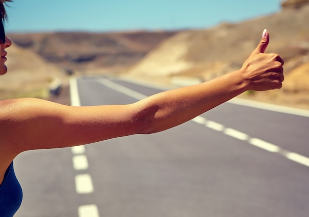 Młody caucasian turysta autostopem wzdłuż drogi w zmierzchu