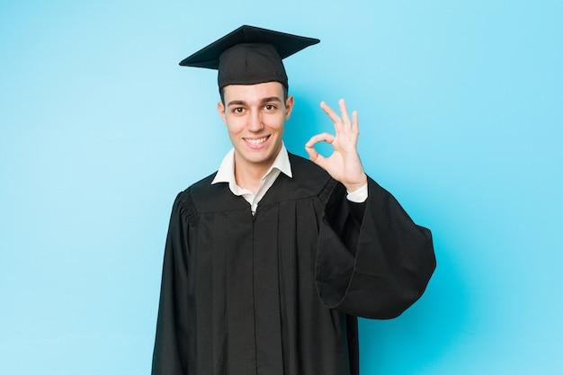 Młody caucasian ukończył człowiek wesoły i pewny siebie, pokazując gest ok.
