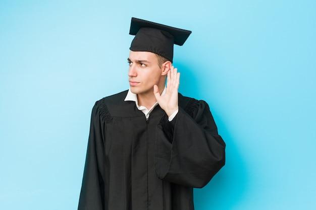 Młody caucasian ukończył mężczyzna próbuje słuchać plotek.