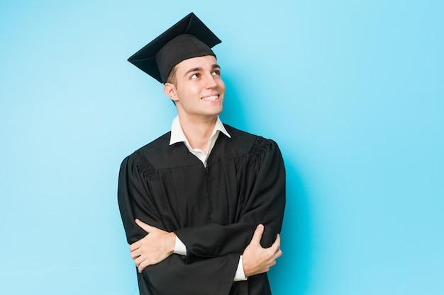 Młody caucasian ukończył mężczyzna uśmiecha się pewnie ze skrzyżowanymi rękami.