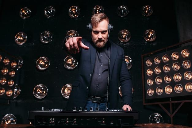 Młody charyzmatyczny brodaty dżokej w mikserze odtwarza słynną muzykę na imprezie w klubie nocnym, wskazując palcem na aparat